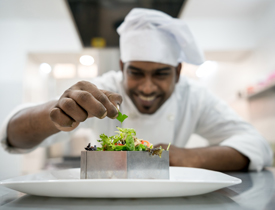 Chef adding garnish to plate.