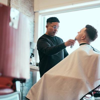 barber shaving clients chin